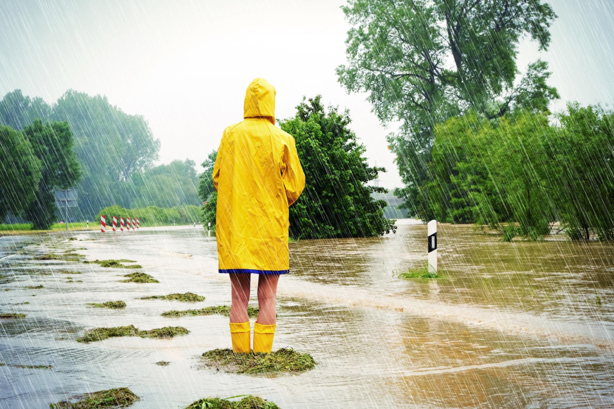 Jente står på en oversvømt vei